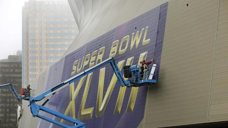 "In this Jan. 15, 2013, photo, workers put up signage for the upcoming Super Bowl on the Superdome in New Orleans. With the Super Bowl in New Orleans Feb. 3 and Mardi Gras falling just nine days later, the city is gearing up for a massive celebration and influx of tourists that locals are calling ""Super Gras."" (AP Photo/Gerald Herbert)"