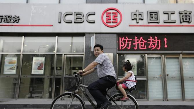 Man cycles bike carrying his daughter past branch of ICBC in Beijing