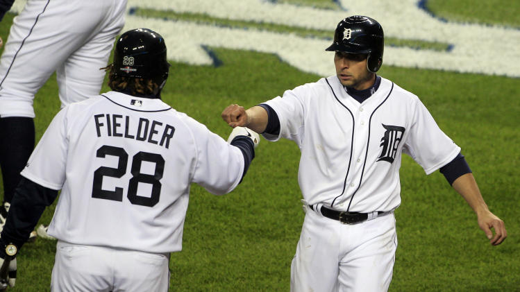 Detroit Tigers' Omar Infante, right is congratulated by teammate Prince Fielder after scoring on a fielding error by Oakland Athletics starting pitcher Jarrod Parker during the third inning of Game 1 of the American League division baseball series, Saturday, Oct. 6, 2012, in Detroit. (AP Photo/Carlos Osorio)