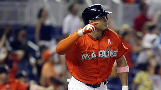 Miami Marlins' Giancario Stanton gestures as he begins to run the bases after hitting the game-winning grand slam against the New York Mets in the ninth inning of a baseball game in Miami, Sunday, May 13, 2012. The Marlins won 8-4. (AP Photo/J Pat Carter)
