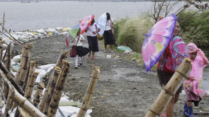 School children walk on a dike reinforced by sand bags in preparation for more rains  brought by tropical storm Kai Tak Tuesday, Aug. 14, 2012 in suburban Malabon City north of Manila, Philippines.  (AP Photo/Pat Roque)