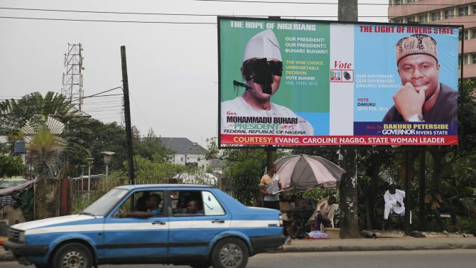 A signboard campaigning for Buhari is defaced along a road in Nigeria's oil hub city of Port Harcourt