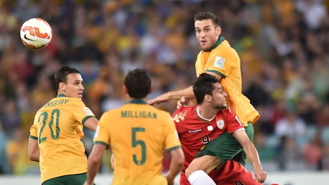 Australia's Matthew Spiranovic (top R) and Oman's Adul Aziz Al-Maqbali of (2nd R) during their Asian Cup match in Sydney on January 13, 2015