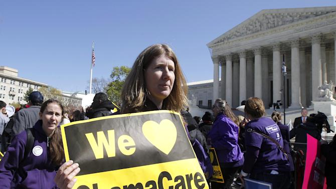 """Holding a sign saying """"We Love ObamaCare"""" supporters of health care reform rally in front of the Supreme Court in Washington, Tuesday, March 27, 2012, as the court continued hearing arguments on the health care law signed by President Barack Obama. Go ahead, call it Obamacare. Obama's re-election campaign has lifted an unofficial ban on using the opposition's derisive term for his health care law. Democratic activists have been chanting, """"We love Obamacare,"""" in front of the Supreme Court. And the campaign is selling T-shirts and bumper stickers that proclaim: """"I like Obamacare."""" (AP Photo/Charles Dharapak)"""