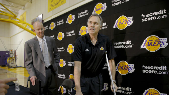 New Los Angeles Lakers coach Mike D'Antoni, right, is accompanied by vice president of public relations John Black as they leave after an NBA basketball news conference in El Segundo, Calif., Thursday, Nov. 15, 2012. Although D'Antoni is still on crutches after his recent knee surgery, he is already at work with the Lakers. (AP Photo/Jae C. Hong)