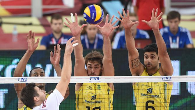 Brazil's Ricardo Lucarelli Santos De Souza, left, Lucas Saatkamp and Leandro Vissotto Neves, right, block an attack from Poland's Michal Kubiak during the FIVB Men's Volleyball World Championships third round group H game between Poland and Brazil in Lodz, Poland, Tuesday, Sept. 16, 2014. (AP Photo/Alik Keplicz)
