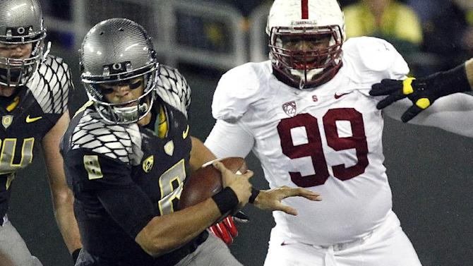Oregon quarterback Marcus Mariota, left, is grabbed by the foot by Stanford defender Shayne Skov during the first half of their NCAA college football game in Eugene, Ore., Saturday, Nov. 17, 2012.(AP Photo/Don Ryan)