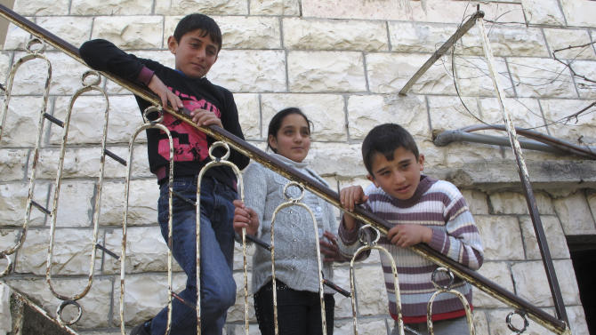 In this March 12, 2012 photograph, Mahmoud al-Alami, 10, left, stands in front of his home with his cousin Farah, center, and brother Mamoun in Beit Umar, West Bank. When Mahmoud was 9-years-old, an Israeli soldier caught him throwing rocks, took him out of his uncle's arms, slung him over his shoulders and took him away. Mahmoud says he was subsequently blindfolded and shackled, slapped and ordered to confess to throwing rocks at Israeli soldiers and identify other children doing the same. (AP Photo/Diaa Hadid)