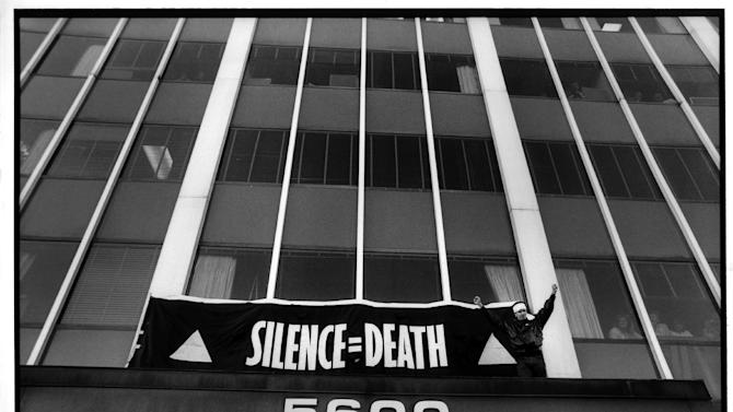 """This Oct. 11, 1988 publicity photo released by Sundance Selects shows Peter Staley in a scene from director, David France's documentary film, """"How to Survive a Plague,"""" a Sundance Selects release. Staley triumphantly finishes hanging a banner over the entrance to the FDA main headquarters, during an HIV AIDS civil disobedience demonstration, in Rockville, Md. (AP Photo/Sundance Selects, Rick Reinhard)"""