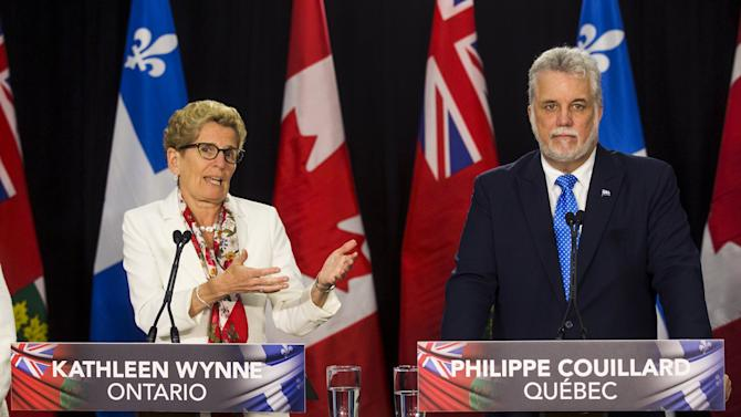 Quebec's Premier Couillard and Ontario's Premier Wynne speak at a news conference during Couillard's visit to Queen's Park in Toronto