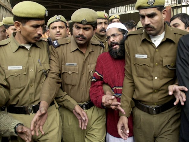 FILE – In this Dec. 17, 2002 file photo, Kashmiri man accused in the parliament attack Mohammed Afzal Guru, second right, is produced at a court in New Delhi, India. Afzal, convicted in the 2001 attack on India's Parliament, has been hanged in an Indian prison, a senior Indian Home Ministry official said Saturday, Feb. 9, 2013. The deadly Islamic militant attack killed 14 people, including the five attackers in 2001. (AP Photo/Aman Sharma, File)