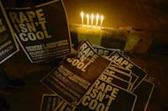 Posters are lit by candle light during a protest in New Delhi on December 31, 2012. Hundreds of protesters clashed with police on Friday outside a New Delhi hospital where a seven-year-old victim of sexual assault was admitted earlier in the day, a police official said