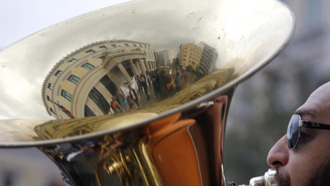 A member of an Athens municipal brass band plays as the Town Hall building is reflected in his instrument, during a demonstration by municipal employees on Monday, Nov. 19, 2012. Several hundred people took part in the protest, against government plans to place 2,000 civil servants on notice ahead of reassignment or potential dismissal. (AP Photo/Petros Giannakouris)