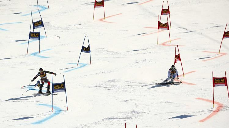 Mancuso of the US competes with Holdener of Switzerland during the Nation Team Event competition at the FIS Alpine Skiing World Cup finals in Lenzerheide