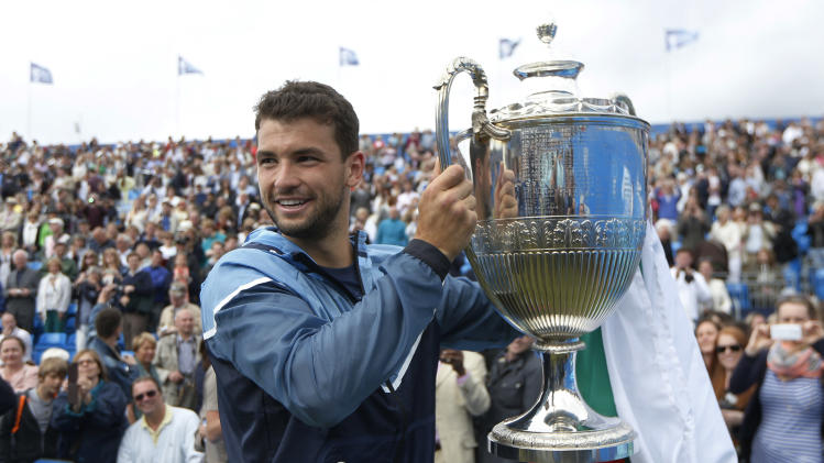 FILE - In this June 15, 2014, file photo, Grigor Dimitrov, of Bulgaria, poses with the trophy after his win against Feliciano Lopez, of Spain, at the end of their Queen's Club grass court championships singles final tennis match in London Heading into the U.S. Open, Roger Federer, Rafael Nadal, Novak Djokovic and Andy Murray have won 36 of the past 38 Grand Slam titles, a stretch dating to the 2005 French Open. Nowadays, there seems to be a growing sense _ or hope, maybe _ among the best of the rest on the men's tennis tour that the quartet might be more vulnerable than ever. (AP Photo/Sang Tan, File)