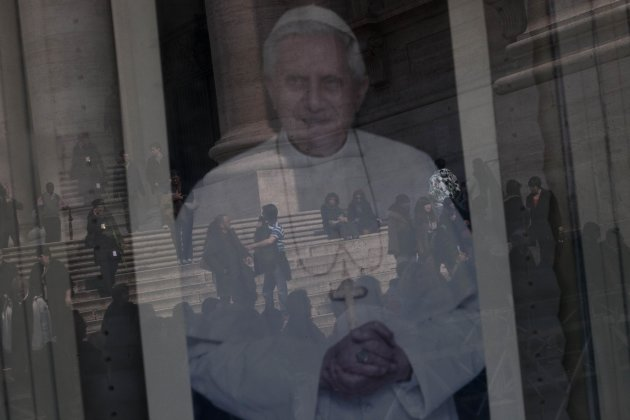 Tourists are reflected in a portrait of Pope Benedict XVI's in St. Peter's Square, a day before the Pope last general audience, scheduled for Wednesday, at the Vatican, Tuesday, Feb. 26, 2013. Pope Be