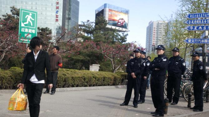 Chinese police officers watch an area near a building that leaders of the unregistered Shouwang house church had told parishioners to gather in Beijing, China, Sunday, April 10, 2011.  Beijing police on Sunday detained at least a dozen worshippers from the Christian house church who were trying to hold services in a public space after they were evicted from their usual place of worship. (AP Photo/Ng Han Guan)