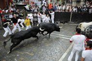 Participants run in front of Dolores Ybarra's bulls during the first bull run of the San Fermin Festival. An elderly man was gored and five other people hurt as daredevils fled half-tonne bulls thundering through the streets Saturday