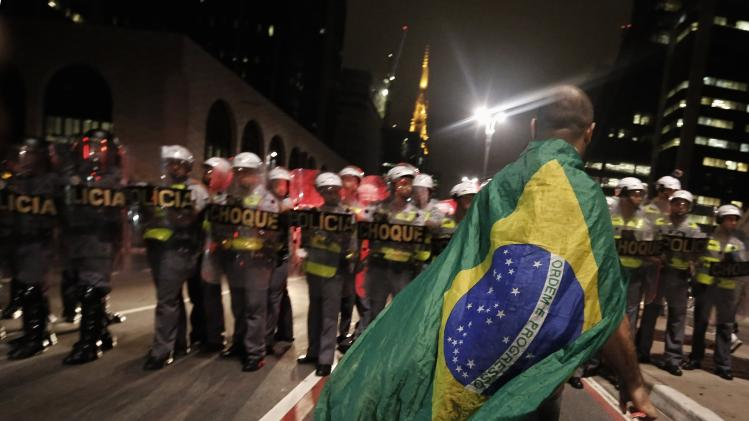 A demonstrator wearing a Brazilian flag walks in front of military policemen during a protest against the 2014 World Cup, in Sao Paulo