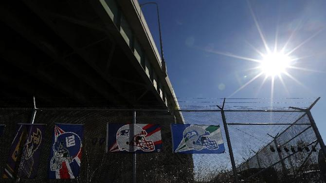 Flags donning the helmets of the New England Patriots, center, and the Seattle Seahawks, right, hang from a fence near other flags for sale, Saturday, Jan. 31, 2015, in Jersey City, N.J. The Patriots face the Seahawks in Super Bowl XLIX on Sunday in Glendale, Ariz