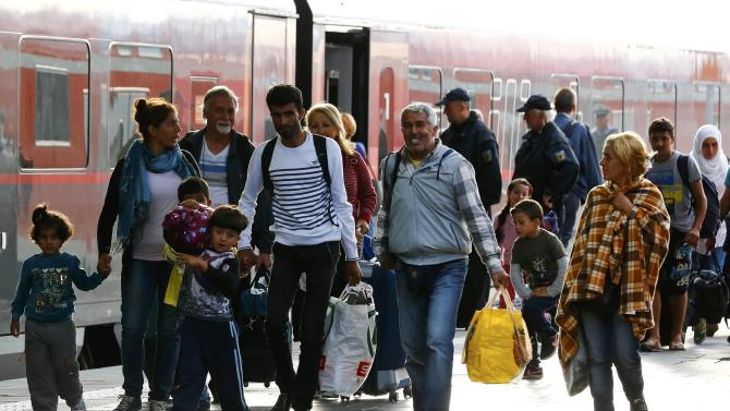 Migrants walk along a train after arriving to the main railway station in Munich