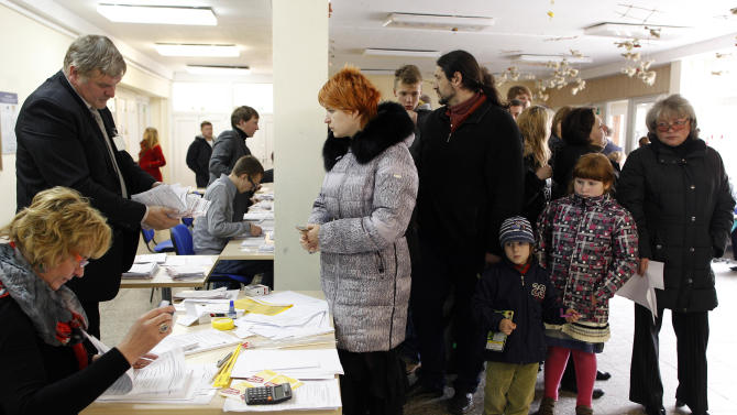 Lithuanian's wait for ballots at a polling station in Vilnius, Lithuania, Sunday, Oct. 14, 2012. Lithuanians are expected to deal a double-blow to the incumbent conservative government in national elections Sunday by handing a victory to opposition leftists and populists and saying 'no' to a new nuclear power plant that supporters claim would boost the country's energy independence. (AP Photo/Mindaugas Kulbis)