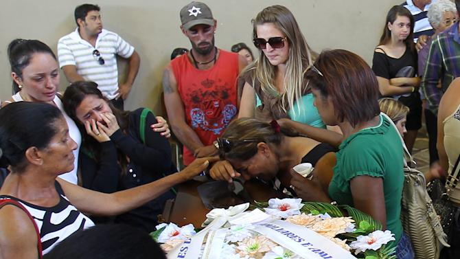 Family members and friends mourn as they stand around a coffin containing the remains of a victim after the bodies were identified at a gymnasium in Santa Maria city, Rio Grande do Sul state, Brazil, Sunday, Jan. 27, 2013.  Flames raced through a crowded nightclub in southern Brazil early Sunday, as panicked partygoers gasped for breath in the smoke-filled air, stampeding toward a single exit partially blocked by those already dead. Officials counted more than 230 bodies that were brought for identification to the gymnasium in Santa Maria,(AP Photo/Nabor Goulart)
