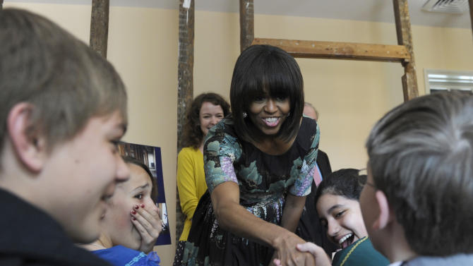 First lady Michelle Obama greets surprised schoolchildren from Willow Springs Elementary School in Fairfax, Va., at the Decatur House, a National Trust for Historic Preservation Site and home to the David M. Rubenstein National Center for White House History, in Washington, Wednesday, May 22, 2013. The events were part of an announcement of a major philanthropic effort to preserve the Decatur House. (AP Photo/Susan Walsh)