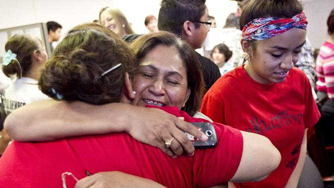 Rosa Maria Soto hugs Eva Monteloneo, right, after hearing President Obama is easing enforcement of immigration laws on Friday, June 15, 2012 in Phoenix.  The new policy offers a chance for hundreds of thousands of younger illegal immigrants to stay in the U.S. and work. (AP Photo/The Arizona Republic, Pat Shannahan)  MARICOPA COUNTY OUT; MAGS OUT; NO SALES
