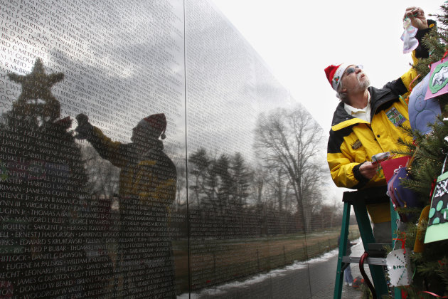 Navy Vietnam Veteran Paul Stancliff, of Mercersburg, Penn., decorates a Christmas tree with cards from around the country at the Vietnam Veterans Memorial in Washington, on Monday, Dec. 20, 2010. (AP