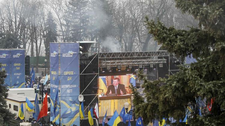 Supporters of Ukrainian President Viktor Yanukovich watch a broadcast of his news conference as they attend a rally in Kiev