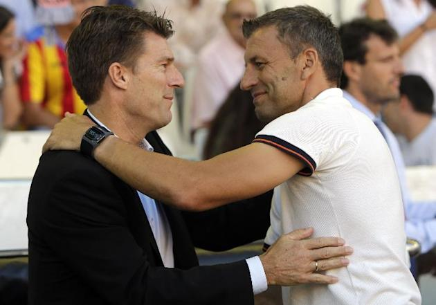 Swansea City's manager Michael Laudrup from Denmark greets Valencia's coach Miroslav Djukic from Serbia before their Europa  League Group A soccer match against Valencia  at the Mestalla stadium in Va