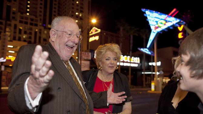 "In this April 1, 2011 photo, Las Vegas mayor Oscar Goodman, left, and his wife Carolyn Goodman greet pedestrians along Fremont Street while visiting businesses during First Friday, a social block party held the first Friday of every month, in Las Vegas. The former Las Vegas mayor branded the city with a larger than life persona. And now he's branded himself again with a memoir. In ""Being Oscar--From Mob Lawyer to Mayor of Las Vegas, Only in America,"" Goodman tells all from his days as a lawyer representing members of the mob to his three terms as the ""happiest mayor in the universe.""  (AP Photo/Julie Jacobson)"