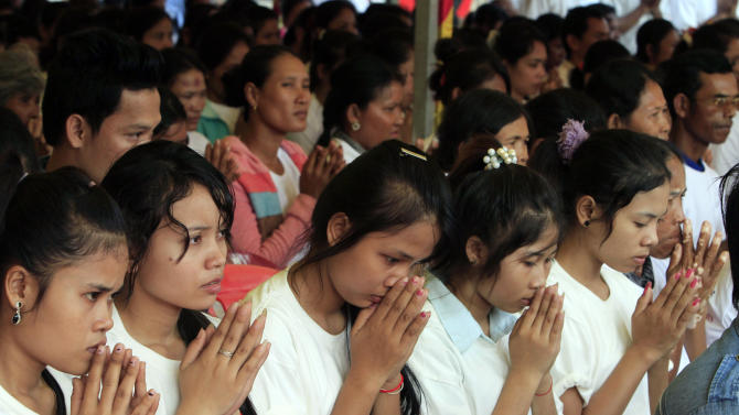 Cambodian garment workers offer prayers during a rally celebrating International Human Rights Day, in Phnom Penh, Cambodia, Monday, Dec. 10, 2012. About 1,000 participants consisting of non-governmental organization activists, garment workers, and international diplomats marched on the street in Phnom Penh, calling for the protection of human rights. (AP Photo/Heng Sinith)