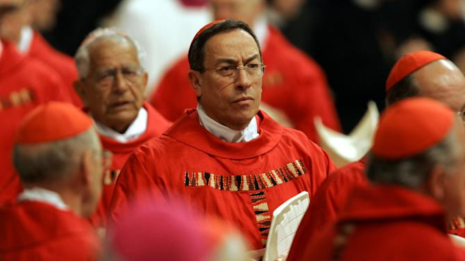 FILE - In this April 12, 2005 file photo Cardinal Oscar Andres Rodriguez Maradiaga of Honduras waits to enter the grottos containing the tomb of Pope John Paul II after a Mass in St. Peter's Basilica, at the Vatican. To many, Honduran Cardinal Andres Rodriguez Maradiaga embodies the activist wing of the Roman Catholic Church as an outspoken campaigner of human rights, a watchdog on climate change and advocate of international debt relief for poor nations.Others, however, see him as a reactionary in the other direction: Described as sympathetic to a coup in his homeland and stirring accusations of anti-Semitism for remarks that some believe suggested Jewish interests encouraged extra media attention on church sex abuse scandals. Both images will follow him into the Sistine Chapel conclave along with other cardinals named as possible successors to Pope Benedict XVI. (AP Photo/Peter Dejong, File)