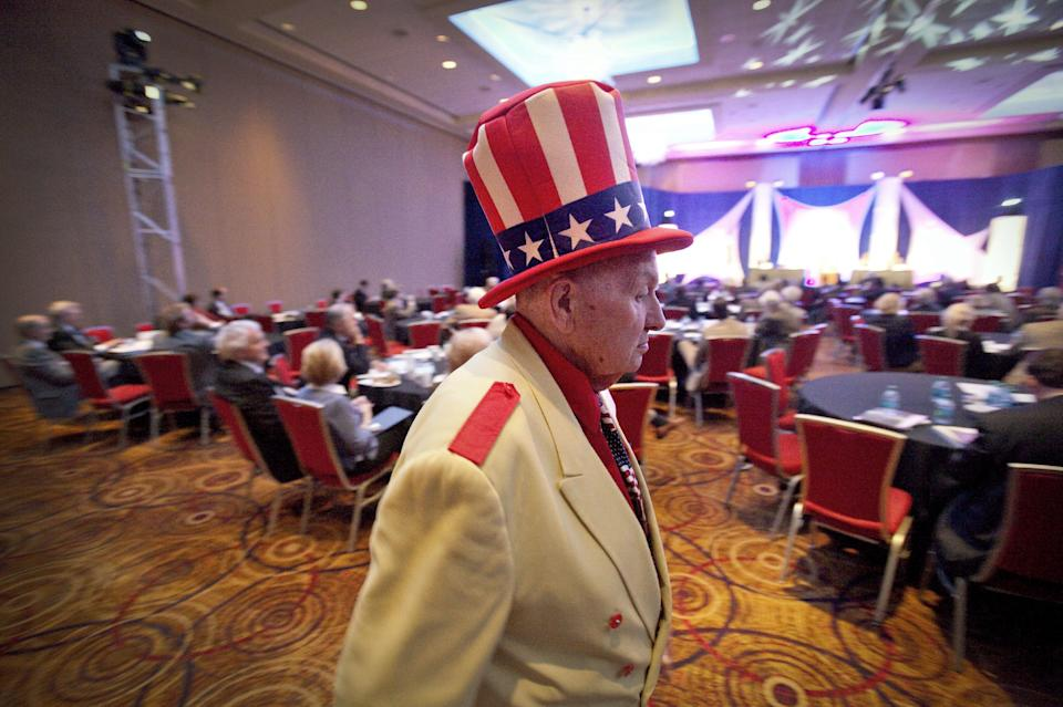 Longtime Mitt Romney supporter Oscar Poole of East Ellijay, Ga., walks to his seat before Republican presidential candidate, Texas Gov. Rick Perry delivered a speech at the Georgia Legislative Briefing, Friday, Sept. 30, 2011, in Atlanta. (AP Photo/David Goldman)