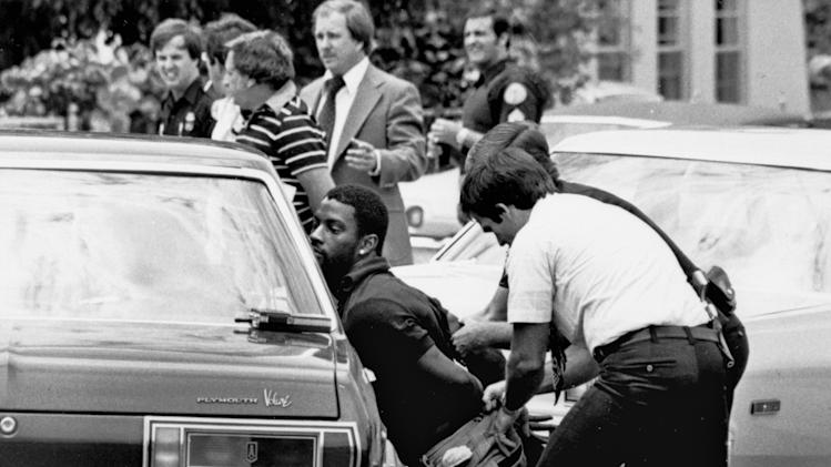 "FILE - In this May 18, 1979 file photo, police handcuff a suspect during a drug raid in Miami. Police said eight were arrested and marijuana was seized. On the occasion of  ""Legalization Day,"" Thursday, Dec. 6, 2012, when Washington's new law takes effect, AP takes a look back at the cultural and legal status of the ""evil weed"" in American history. (AP Photo/Al Diaz, File)"