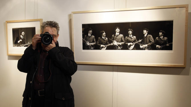 Photographer Mike Mitchell takes pictures of photographers whilst he stands by some of his photographs of The Beatles where they are being exhibited at a hotel in London, Friday, June 10, 2011. The previously unseen photographs by US photographer Mike Mitchell were taken during the1964 visit to America. The collection of 50 pictures entitled 'Beatles Illuminated' is expected to realise 100,000 US Dollars (61,500 pounds) when they are auctioned in New York on July 20. (AP Photo/Kirsty Wigglesworth)