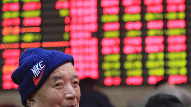 An investor smiles in front of the stock price monitor at a private securities company in Shanghai, China, Friday, Dec. 13, 2013. Asian stock markets mostly posted tentative gains Friday as investors prepared for the U.S. Federal Reserve's decision next week on whether to reduce its monetary stimulus. (AP Photo)