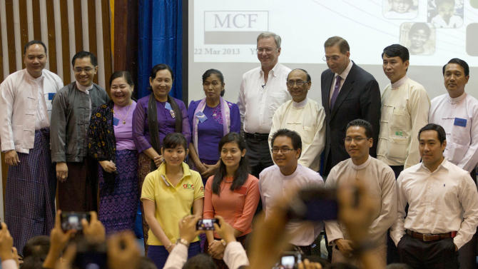 Google Executive Chairman Eric Schmidt, center, poses for photos with a group of Myanmar students and entrepreneurs after an interactive session at a technical university in Yangon, Myanmar, Friday, March 22, 2013. Schmidt on Friday urged Myanmar's government to allow private businesses to develop the country's woeful telecommunications infrastructure, emphasizing the importance of competition and free speech. (AP Photo/Gemunu Amarasinghe)