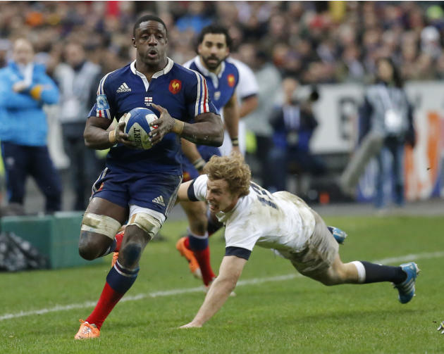 France's Yannick Nyanga, left, is tackled by England's Luther Burrell, right, during their Six Nations international rugby union match between France and England at Stade de France stadium in