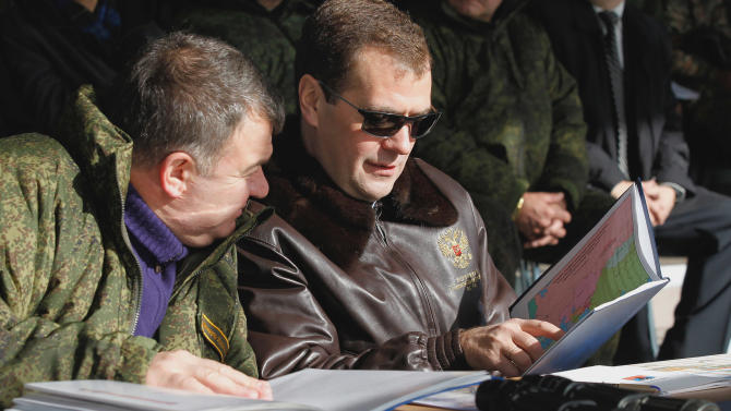 Russian President Dmitry Medvedev and Defense Minister Anatoly Serdyukov, left, look at maps during Center-2011 military maneuvers in the Chelyabinsk region of Russia on Tuesday, Sept. 27, 2011. (AP photo/ RIA Novosti, Dmitry Astakhov, Presidential Press Service)