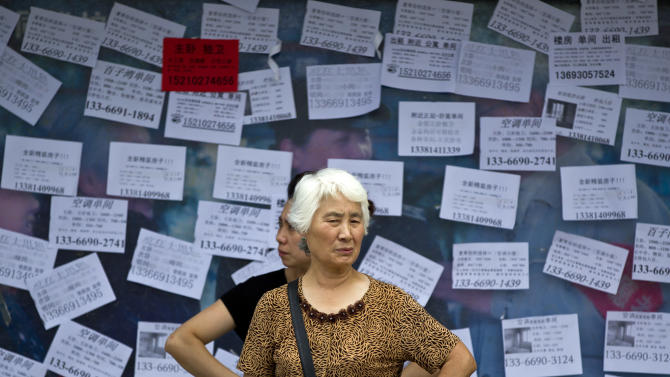 A woman frowns at a bus station while a government propaganda photo behind her is covered by apartment rental advertisements in Beijing, China, Friday, July 13, 2012. China's economic growth slowed to a new three-year low in the latest quarter as exports and consumer spending weakened. (AP Photo/Alexander F. Yuan)