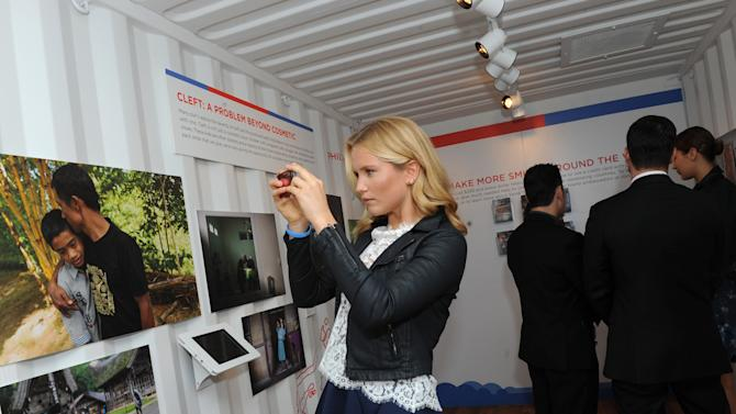 """IMAGE DISTRIBUTED FOR SMILE TRAIN - Sailor Brinkley Cook, IMG model, photographs the Smile Train multimedia """"When You're Smiling"""" installation at Photoville, Thursday, Sept. 18, 2014, at Pier 5 in Brooklyn, New York.   Smile Train is an international children's cleft charity.  (Photo by Diane Bondareff/Invision for Smile Train/AP Images)"""