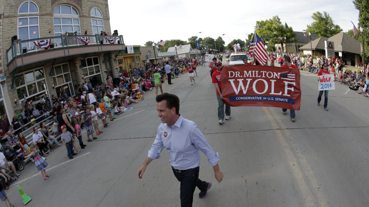 In this photo taken July 4, 2014, Milton Wolf, works the crowd at a Fourth of July parade in Wamego, Kan. Wolf has tea party backing in his quest to unseat three-term GOP incumbent Pat Roberts. (AP Photo/Charlie Riedel)