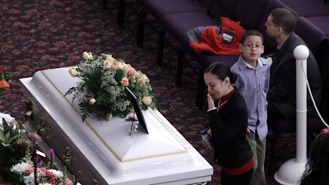 Christina Jimenez, sister of Sarai Sierra, pauses at her casket during her funeral at the Christian Pentecostal Church, in the Staten Island borough of New York,  Friday, Feb. 15, 2013.  The 33-year-old mother of two was killed while vacationing alone in Turkey. Sierra disappeared Jan. 21, and her body was discovered 12 days later near Istanbul's ancient city walls. (AP Photo/Richard Drew)