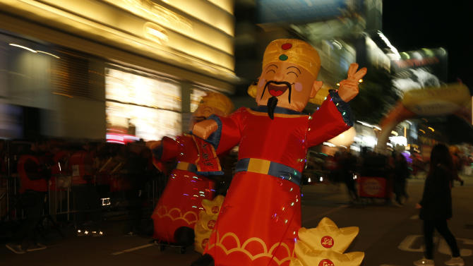 Inflatable dolls depicting the Chinese God of Wealth are displayed during a Lunar New Year parade on the first day of the Lunar New Year of the Monkey in Hong Kong