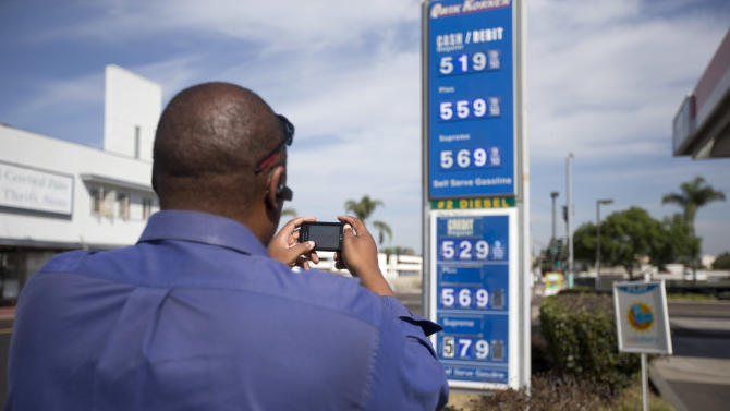 Carl Smith stops to take a picture of high gasoline prices posted at a gas station Friday, Oct. 5, 2012, in San Diego. Californians woke up to a shock Friday as overnight gasoline prices jumped by as much as 20 cents a gallon in some areas, ending a week of soaring costs that saw some stations close and others charge record prices. The average price of regular gas across the state was nearly $4.49 a gallon, the highest in the nation, according to AAA's Daily Fuel Gauge report. (AP Photo/Gregory Bull)