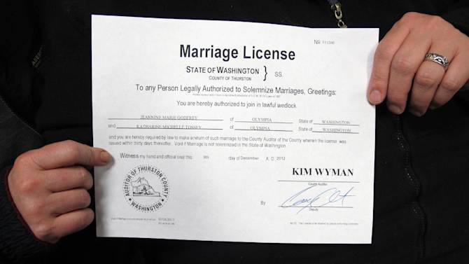 Jeannine Godfrey, left, and Katharine Tossey, right, hold their marriage license at the Thurston County Courthouse on Thursday, Dec. 6, 2012, in Olympia, Wash. Washington state's new voter-approved gay marriage law took effect Thursday, and couples across the state began picking up licenses and can start marrying as soon as Sunday. (AP Photo/Rachel La Corte)