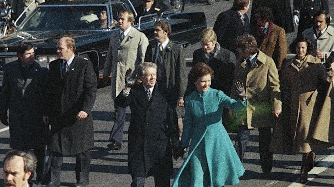 FILE - This Jan. 20, 1977 file photo shows President Jimmy Carter and First Lady Rosalynn Carter waving as they walk down Pennsylvania Avenue in Washington after Carter was sworn in as the nation's 39th president. At some point on Inauguration Day, if all goes expected, the president's limousine will slow to a stop on its journey down Pennsylvania Avenue from the Capitol to the White House. A Secret Service agent will open the rear passenger door, and the newly sworn-in president will emerge from his car for a several-minute stroll. The crowd will cheer. The president will wave. In that moment, Pennsylvania Avenue is America's red carpet. And the president is the only celebrity on it. The victory walk has become an iconic inaugural moment, one expected by the public and the press.  And though the tradition dates only to President Jimmy Carter, it has already developed an air of inevitability and predictable patterns.  (AP Photo, File)
